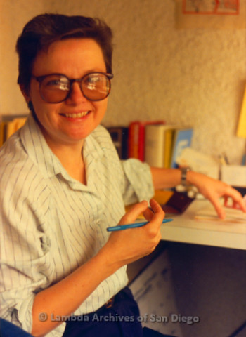 P149.003m.r.t Christine Kehoe sitting at a desk smiling with a pen and stack of papers