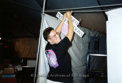 P119.005m.r.t San Diego Pride: A Lambda Archives member hangs a poster up in LASD booth