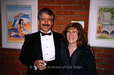 P237.020m.r.t Center Events: Karen Marshall and a man posing in front of watercolor paintings