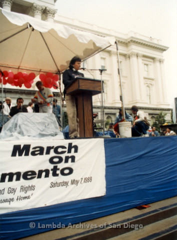 P019.101m.r.t March on Sacramento 1988 / Pre Parade gathering: Woman on stage speaking in front of city hall.