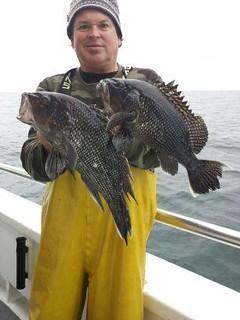 Photo of man holding black sea bass