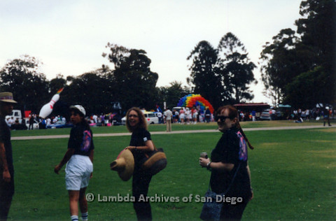 P119.006m.r.t San Diego Pride: Lambda Archives members (including Kate Johnson, center) walking across grass, parade floats in background