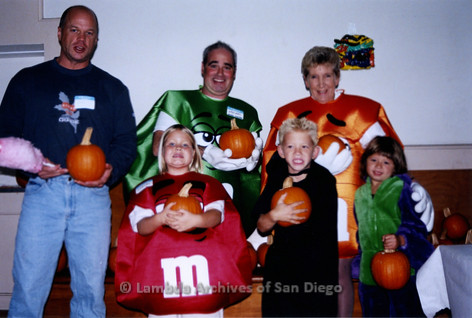 P184.018m.r.t Nightmare On Normal Street: Group of adults and children dressed as M&M's in various colors, holding pumpkins.