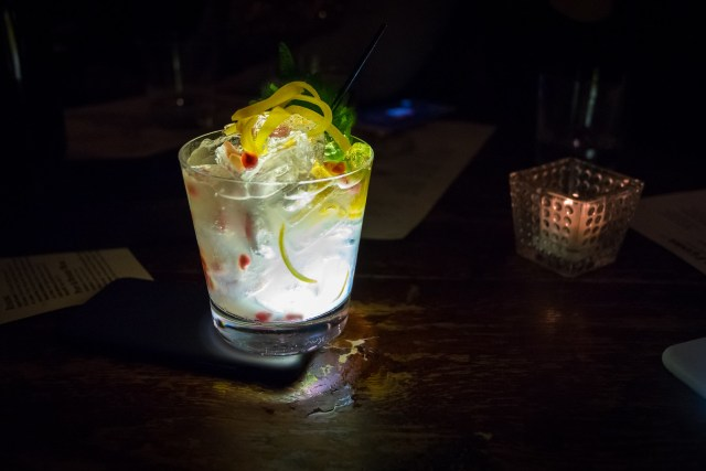 a bright and lemony cocktail, garnished with a shiso leaf