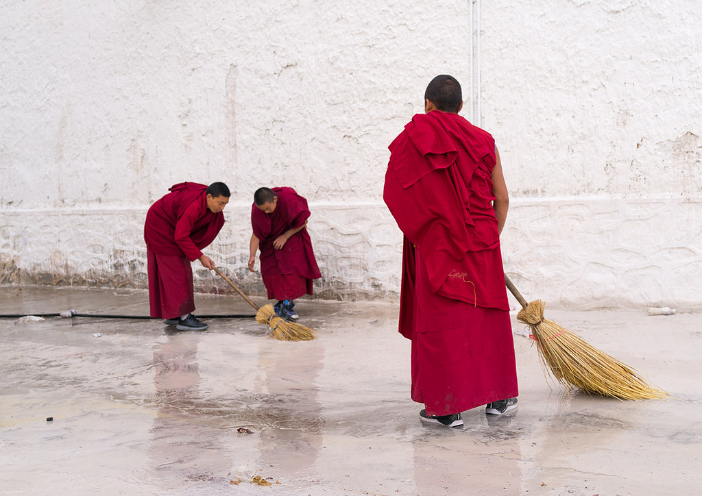 Buddhist monks in red robes are cleaning Rongwo monastery, Tongren County, Longwu, China