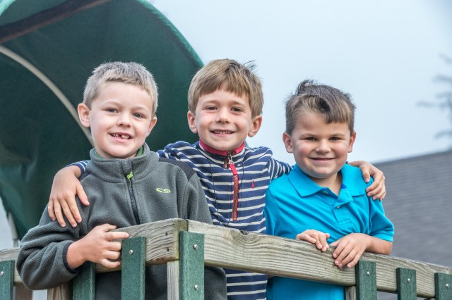 Photograph of three boys posing on the top of a play structure.