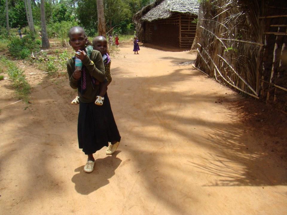 joven con niño en su espalda su gente pequeña aldea Zanzíbar Tanzania 13