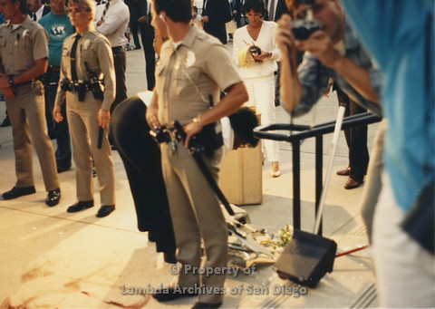P024.092m.r.t Myth California Protest, San Diego, June 1986: 3 police officers, one person taking a photo