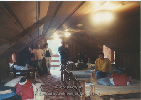 P001.187m.r.t Retreat 1991: group photo inside a cabin (dark photo)