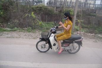 Frau mit Maske auf Scooter