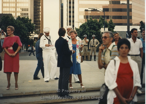 P024.143m.r.t Myth California Protest, San Diego, June 1986: Candid shot of people, 2 men in navy outfits, police officers in the background