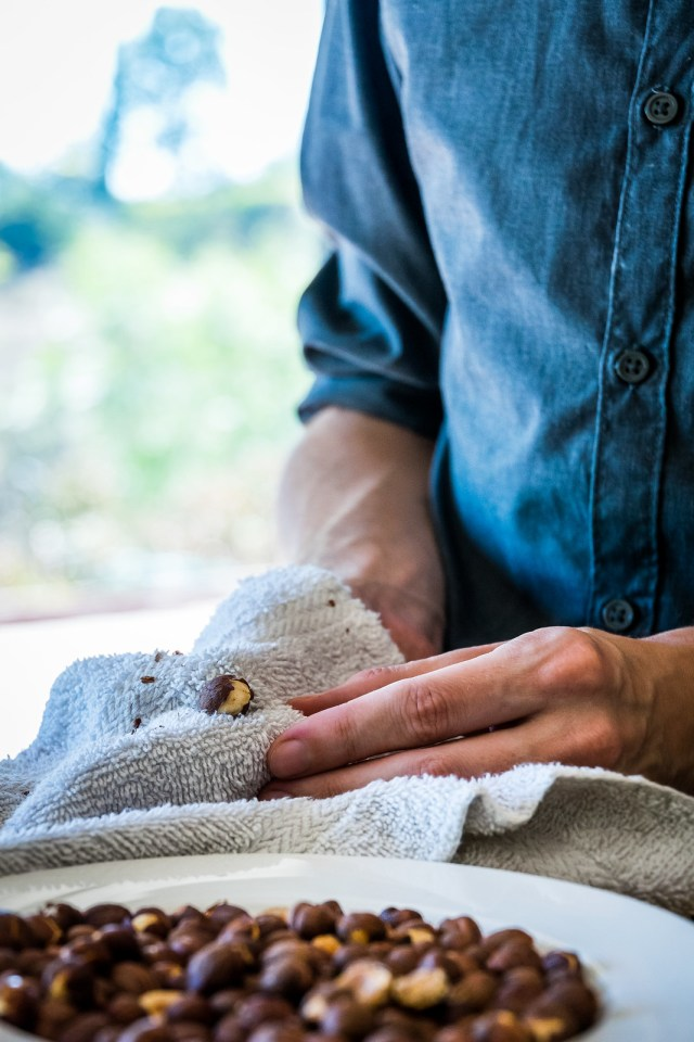 using a washcloth to rub the skins off the hazelnuts