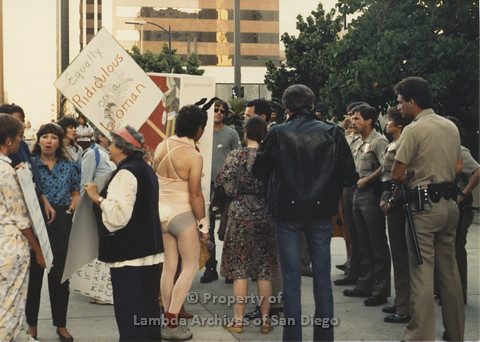 P024.105m.r.t Myth California Protest, San Diego, June 1986: Candid shot of crowd, man in bunny outfit holding sign (Equally Ridiculous on a Woman) in center, police officers to the right