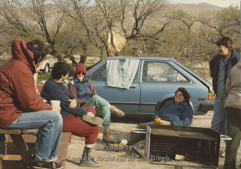 P024.069m.r.t Cathy Moore's 34th Birthday, Halley's Comet Weekend, Anza Borrego Desert 1986: women sitting in front of a blue car