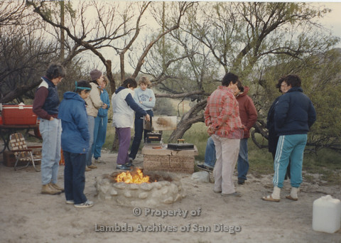 P024.061m.r.t Cathy Moore's 34th Birthday, Halley's Comet Weekend, Anza Borrego Desert 1986: 10 women huddled around campfire waiting for BBQ.