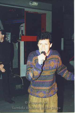 P001.314m.r.t Date Auction: man in patterned sweater holding a microphone man in black shirt standing behind him