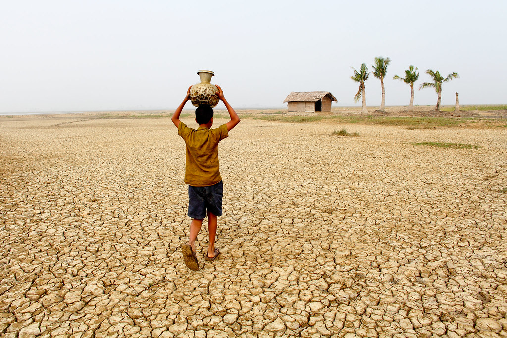 A young boy carries water home through a parched landscape… | Flickr
