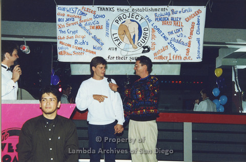 P001.325m.r.t Date Auction: two men holding hands onstage, man in patterned sweater holding microphone for man in white sweater