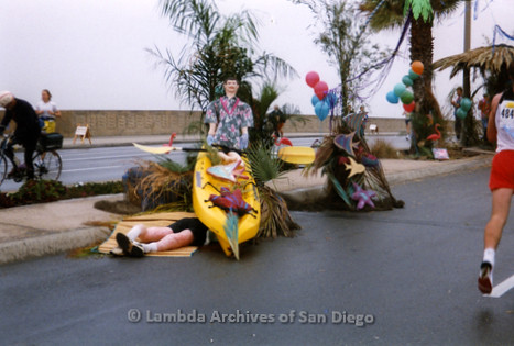 P263.011m.r.t Front Runners and Walkers of San Diego: Man resting under marathon decorations on the side of the road