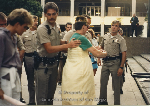 P024.134m.r.t Myth California Protest, San Diego, June 1986: police officers around a woman in a yellow dress and a crown, an officer with his hands on the woman in a yellow dress