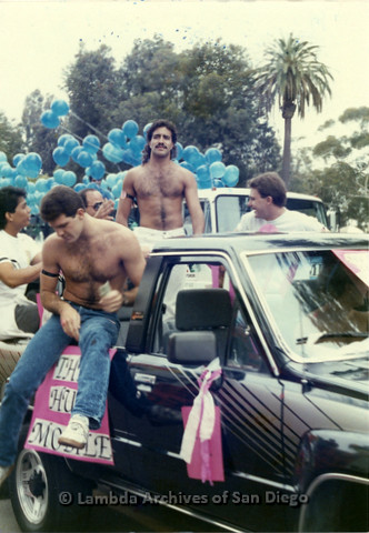 """P018.012m.r.t San Diego Pride Parade 1988: Men riding in back of truck labeled """"The Hug Mobile"""""""