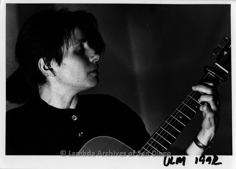 1993 - San Diego Native, Zanne in Germany: Lesbian Performer, Close-up of Zanne playing guitar.