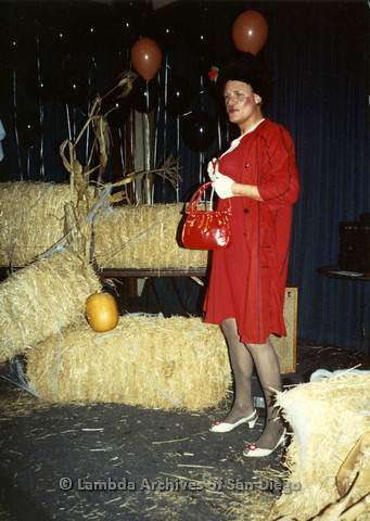 P099.075m.r.t Halloween: A man in red dress and heels, in front of hay bales and balloons