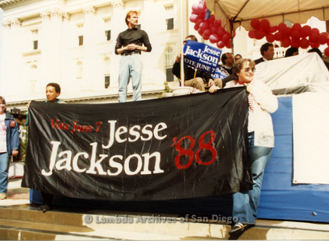 """P019.158m.r.t March on Sacramento 1988 / Pre Parade gathering: Man on stage with two people holding a sign that reads """"Vote June 7 Jesse Jackson '88"""" beneath stage"""