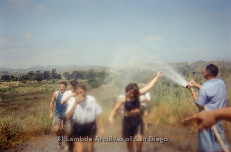 P263.017m.r.t Front Runners and Walkers of San Diego at 1998 Mud Pride: Group photo of participants on the trail; One woman is being hosed down with water