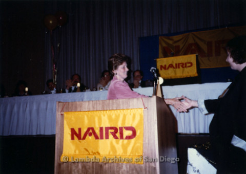 P168.004m.r.t National Association of Independent Record Distribution event: Karen Merry shaking hands with woman at podium