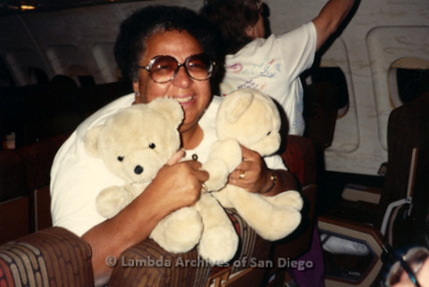 """The Magic Music Makes"" San Diego Women's Chorus (SDWC) first choral festival with Sister Singers 1991: Chorus Director, Cynthia Lawrence Wallace (SDWC's director) hugs teddy bears on the airplane"
