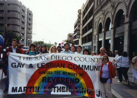 "P341.017m.r.t Group standing outside with a banner reading, ""The San Diego County Gay & Lesbian Community honors the memory of reverend Martin Luther King, JR."""