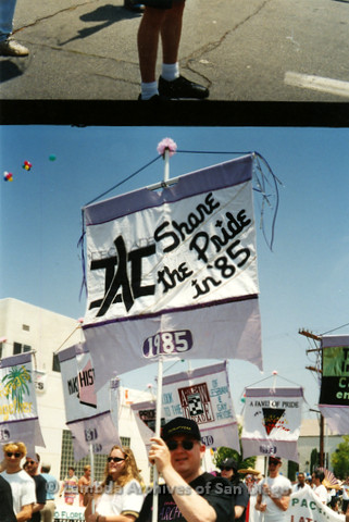 "P119.010m.r.t San Diego Pride 1993: A man holding up a banner commemorating the 1985 Pride theme: ""Share the Pride"""