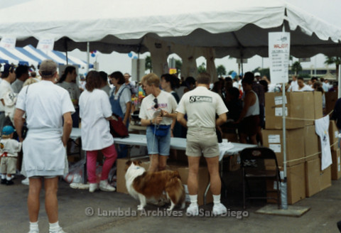 P240.046m.r.t The Center at AIDS Walk 1994: Man with dog standing around other walkers by tent
