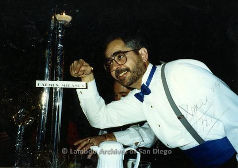 "P099.028m.r.t A man pointing at an award for ""Carmen Miranda"" ""Xmas 89"" written on photo"