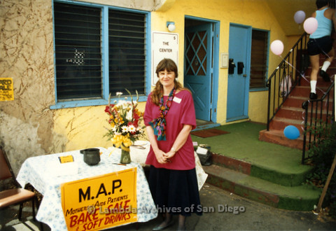 "P019.320m.r.t M.A.P. Bake Sale/Art Auction: Barbara Peabody standing next to table with sign that reads: ""M.A.P. MOTHERS of AIDS PATIENTS BAKE SALE & SOFT DRINKS"""