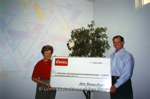 P237.013m.r.t Center Events: Man and woman holding large check made out to The Center for $5,000 from Coors Brewing Company