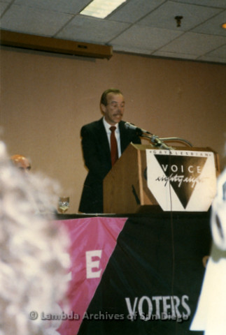 """P341.016m.r.t Dr. Brad Truax speaking at podium with sign in front that reads """"Gay & Lesbian Voice eighty eight"""""""