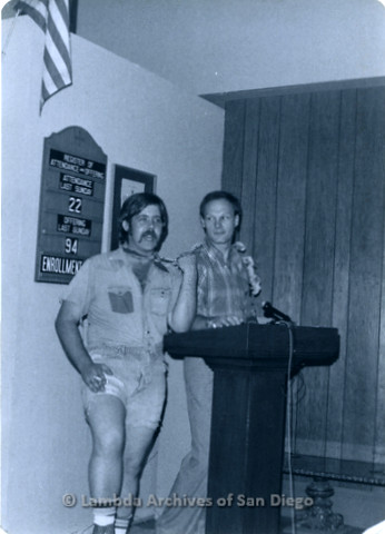 P355.079m.r.t MCC Oceanside Benefit 1976: Two men speaking on the podium