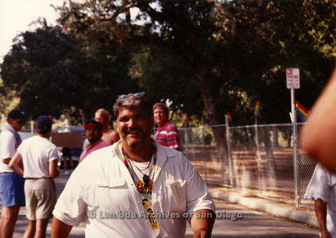 P099.044m.r.t Steve Leitner (?) wearing rainbow lanyard and walking past Pride grounds