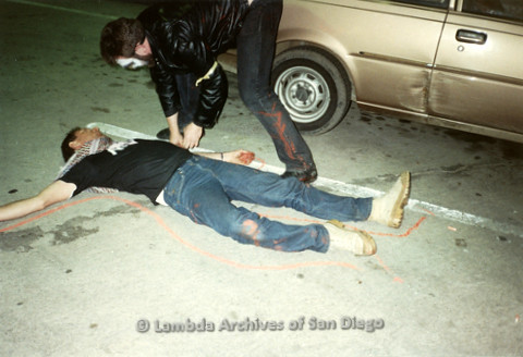 """P019.349m.r.t Los Angeles """"Die In"""" 1988: Man laying on ground while another man draws red chalk outline around him"""