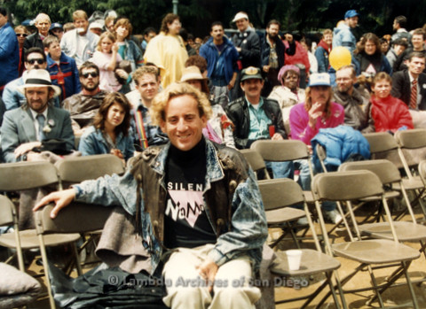 P019.103m.r.t March on Sacramento 1988 / Pre Parade gathering: Man sitting in audience