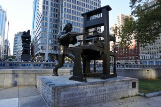 Benjamin Franklin working his press