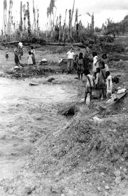 Locals Around Drainage Pipe, 1944