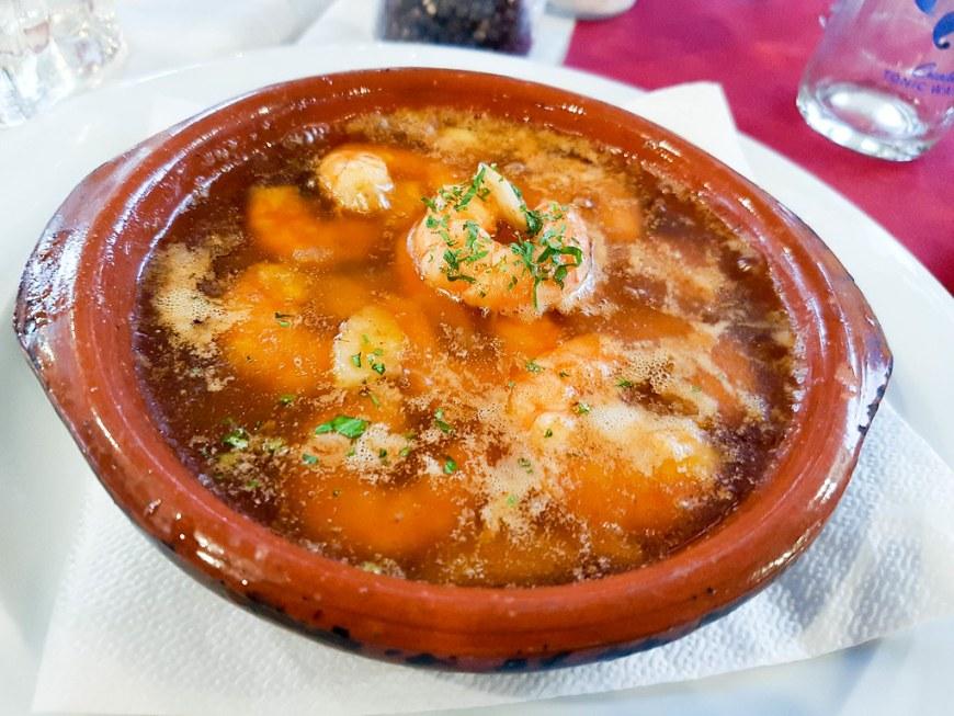 A terracota bowl of prawns pil-pil