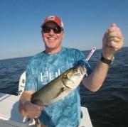 Photo of many holding a bluefish.