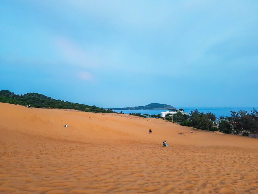 People sliding down the red sand dunes slopes
