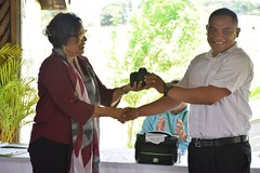 Minister within the Ministry of Indigenous Peoples Affairs, Valerie Garrido-Lowe hands over a REDD+ Guyana package to KMCRG's President and Toshao of Yupukari Russian Dorrick.