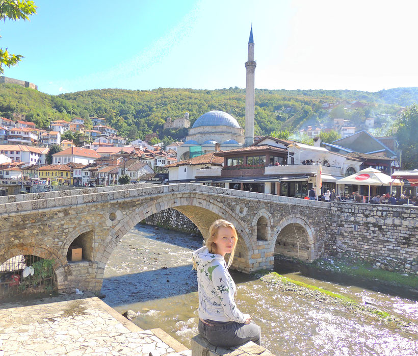 A woman standing by the river looking at the camera. Behind her there is an old bridge and a mosque with one minarette