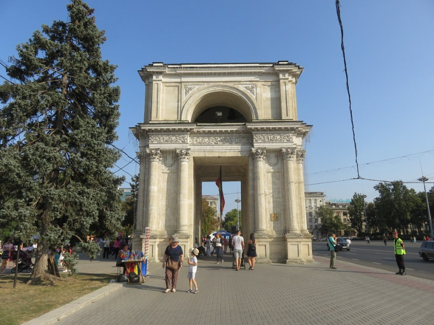 People passing by a small replica of the Arch of Triumph in Paris